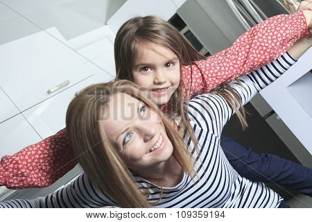 A Mother with daughter standing in kitchen. Interior portrait.