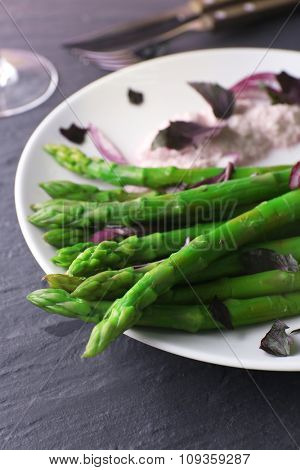 Fresh asparagus dish with red chopped onion on white plate against grey wooden background, close up