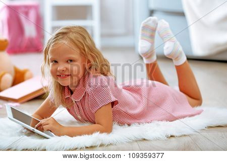Little girl with tablet in the room