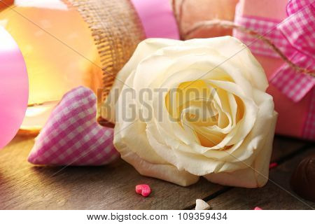 A white rose and a gift in the box, on wooden background, close-up