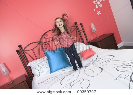 Beautiful little girl jump on bed