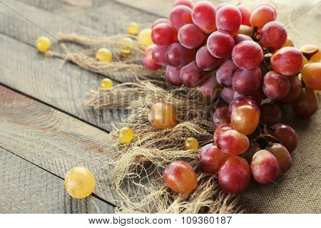 Juicy purple grapes, on wooden background