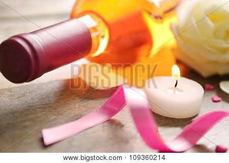 A bottle of wine, a candle and a white rose, on wooden background