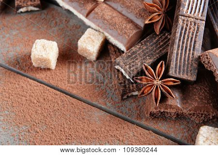 Chocolate sweets with powder on wooden background