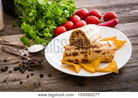burrito with chips on plate and vegetables on a wooden background
