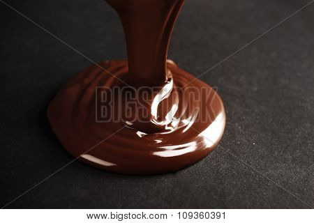 Chocolate poured on dark surface