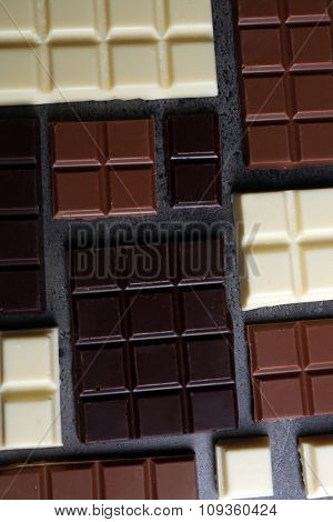 Different chocolate pieces on gray background