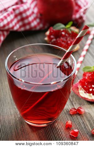 A glass of tasty juice and garnet fruit, on wooden background, close-up