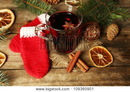 Christmas composition of mulled wine, cinnamon, pine and red knitted mittens on wooden background