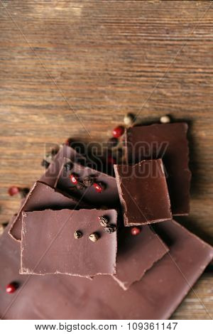 Black chocolate pieces with pepper on wooden background