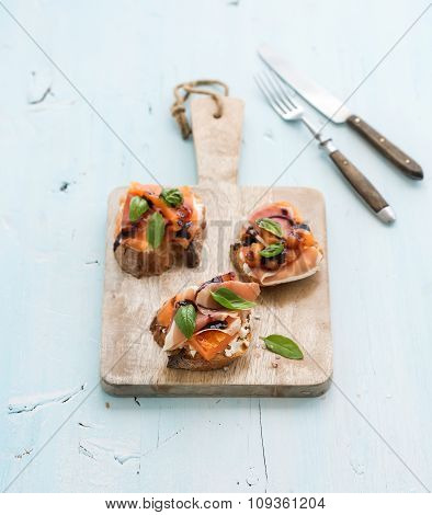 Bruschettas with Prosciutto, roasted melon, soft cheese and basil on wooden serving board over light