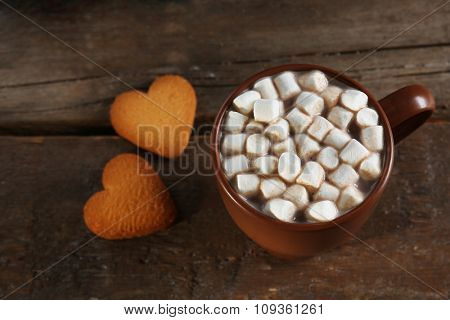 A cup of tasty cocoa and marshmallow on wooden table