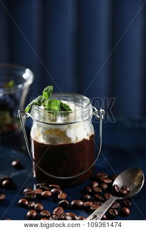 Chocolate dessert in glass with whipped cream on color wooden background