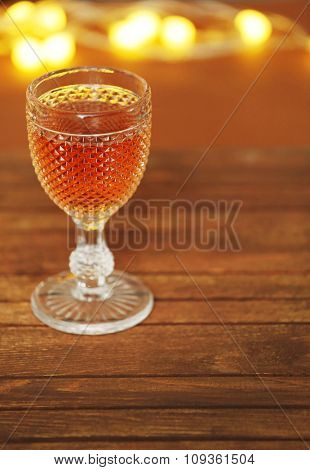 A glass of pink wine on wooden table background