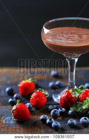 Chocolate dessert in glass and fresh berries on color wooden background