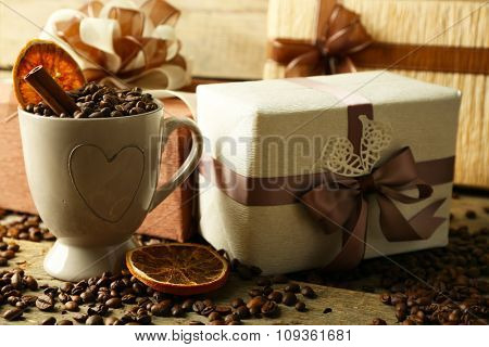 Beautiful gifts and coffee grains in mug, on wooden background