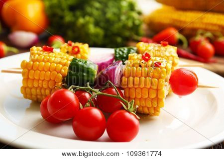 Delicious grilled corn and vegetables on white plate