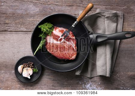 Marbled beef steak on pan and spices on wooden background