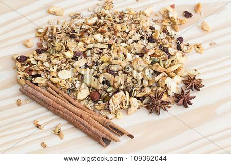 Pile Of Granola Cereal And Cinnamon Sticks On The Wood Background