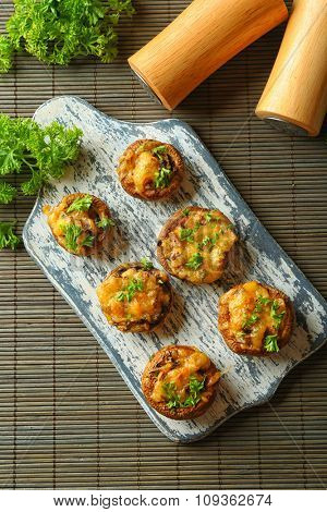 Stuffed mushrooms on wooden board, on table background