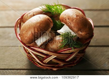 Mushrooms in basket on wooden surface
