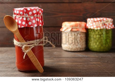 Glass jar of hot tomato sauce, on wooden background