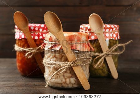 Glass jars of preserved peas and beans on wooden background