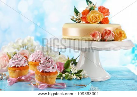 Tasty cupcakes and cake, on table, on light background