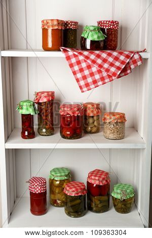 Jars with pickled vegetables and beans on wooden shelves