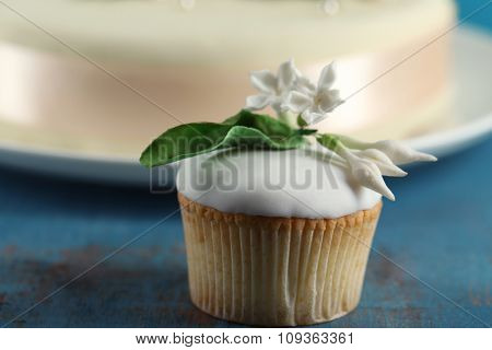 Tasty cupcake and cake, on table, on color background