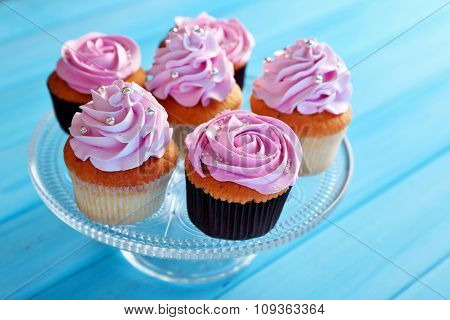 Tasty cupcakes on color wooden background