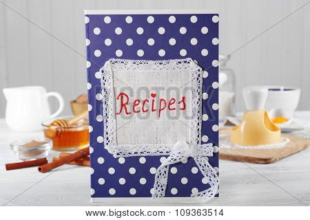 Recipe book on a table with ingredients for baking