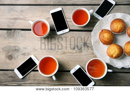 Smart phones, cups with tea and muffins, on wooden table background