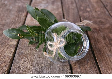 Fresh bay leaves in glass jar on vintage wooden table