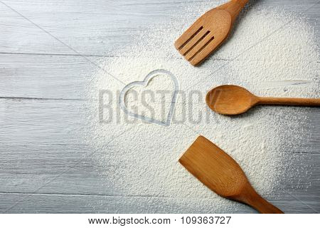 Heart of flour and kitchen utensils on wooden background