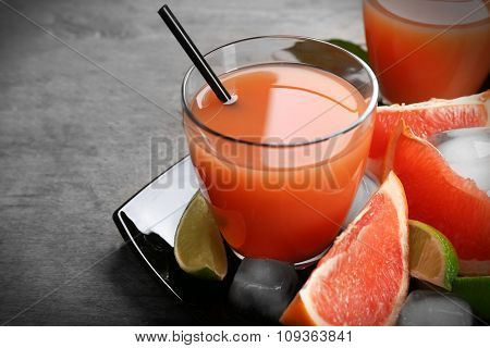 Citrus juice and fresh fruits on black plate