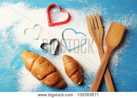Heart of flour, croissants on color wooden background