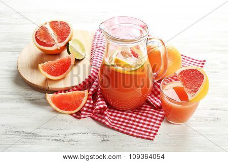 Jar of citrus juice and fresh fruits on light wooden background