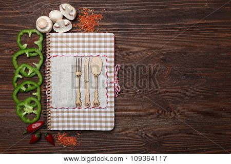 Decorated composition of recipe book and ingredients on wooden background, copy space