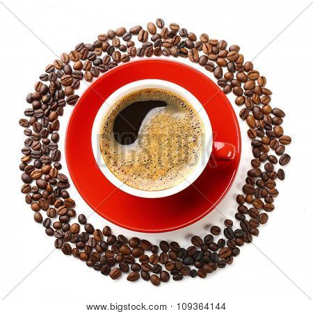 A red cup of tasty drink and scattered coffee grains in the shape of circle, isolated on white, top view