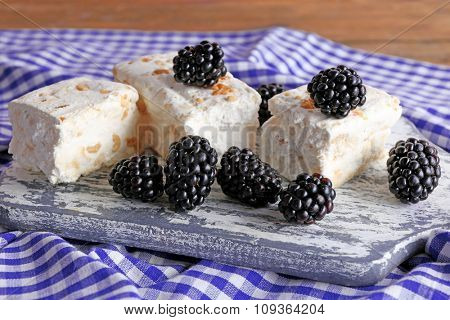 Sweet nougat with nuts and blackberries on cutting board close up