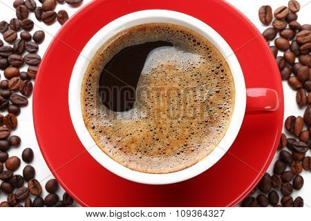 A red cup of tasty drink and scattered coffee grains, close-up, top view