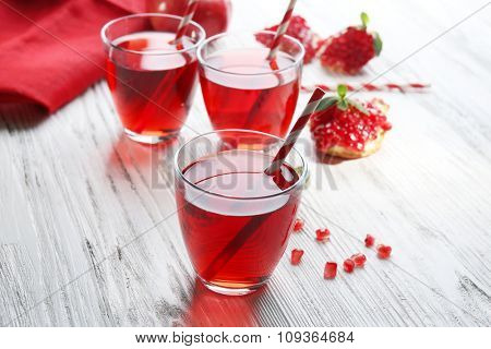 Three glasses of tasty juice and garnet fruit, on wooden background