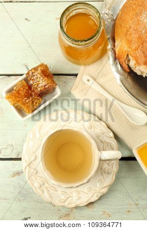 Honeycomb, bowl with honey, cup with herbal tea on color wooden background