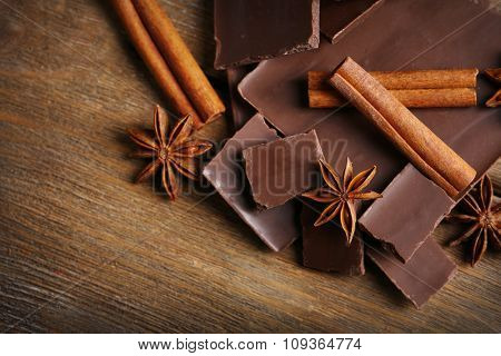 Black chocolate pieces with spices on wooden background