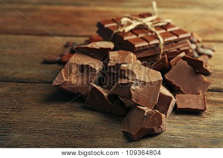 Chocolate pieces, shavings and cocoa beans on color wooden background