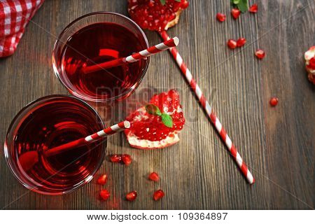 Two glasses of tasty juice and garnet fruit, on wooden background, top view