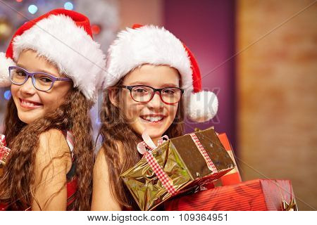 Happy sisters holding gifts in front of christmas tree