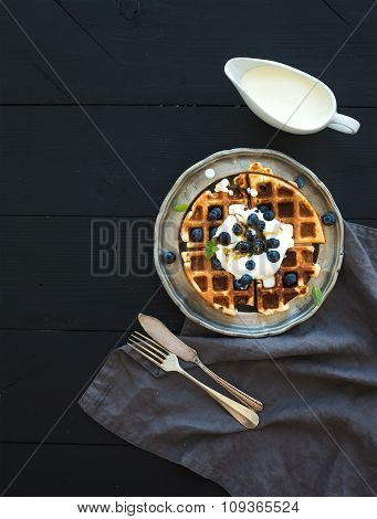 Soft Belgian waffles with blueberries, honey and whipped cream on vintage metal plate over black woo