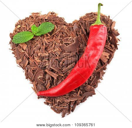 Dark chocolate shavings in shape of heart  with chili pepper isolated on white